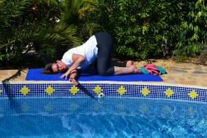 Thread needle pose during yoga to release shoulder tension at La Crisalida Retreats, health, wellbeing and yoga retreat, Spain
